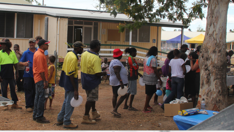 Locals and visitors line up for a BBQ lunch at the community opening of the Mums 'n' Bubs clinic