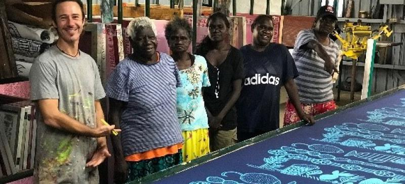 A man in paint spattered t-shirt and 5 Aboriginal women in different coloured clothes stand behind a work bench with a dark blue cloth over it showing pale blue traditional Indigenous shapes and designs.