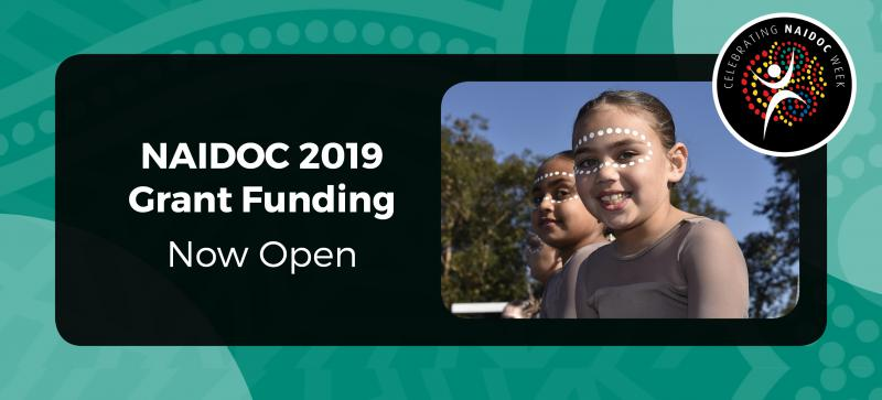 Green Indigenous print background with small black rectangle with the NAIDOC logo in the top right corner. The rectangle contains writing: NAIDOC 2019 Grant Funding Open Now. A photograph in the middle has 2 female dancers smiling.