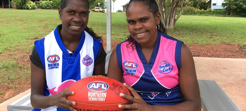 Two young Aboriginal women sit at a picnic table, holding an AFL football in their hands. One wears a blue and pink football jumper, the other wears a blue and white striped football jumper. In the background is a grassed area, trees and buildings.